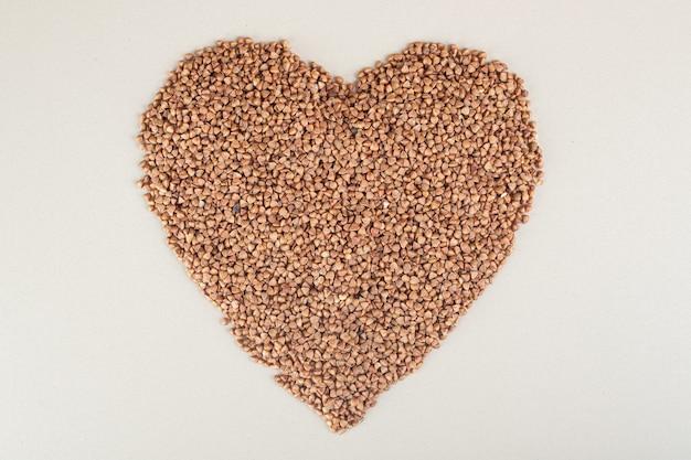 Semi di grano saraceno a forma di cuore su cemento.