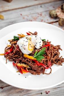 Buckwheat soba noodles wok beef and poached egg