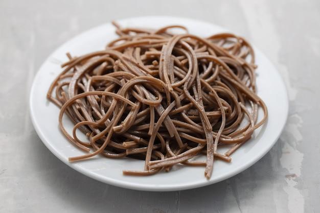 Гречневые спагетти на белой тарелке на керамическом фоне