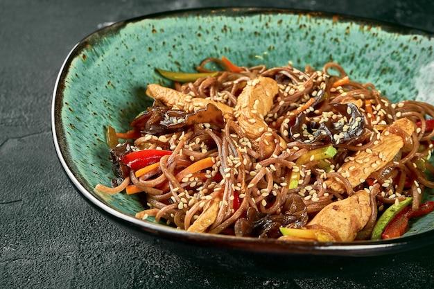 Гречневая лапша удон вок с курицей, овощами, соусом в зеленой тарелке. крупным планом, выборочный фокус