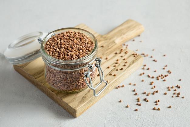 Гречневые сырые зерна в стеклянной банке на деревянной разделочной доске заделывают на сером фоне. здоровое, диетическое питание. органический, углеводный продукт. хранение продуктов.