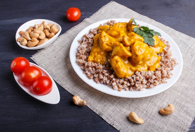 Buckwheat with chicken curry sauce with cashew on black wooden surface.