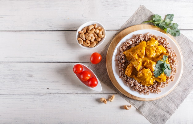 Buckwheat with chicken curry sauce with cashew on white wooden background.