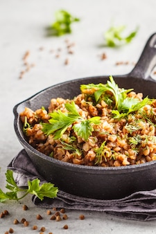 Buckwheat with meat in a cast iron pan on a white background.
