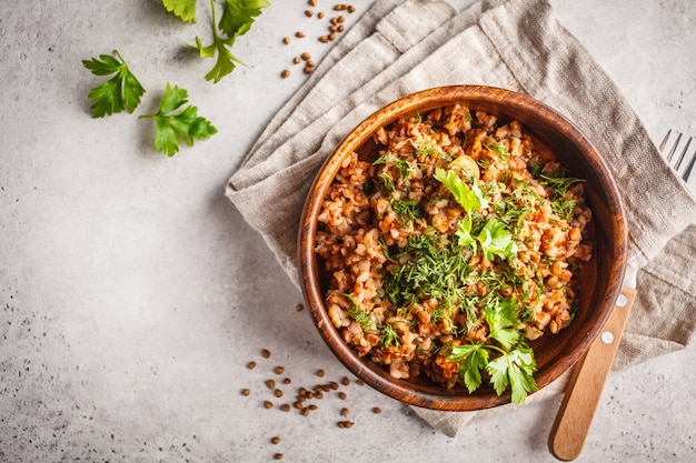 Buckwheat with meat in a wooden bowl on a white background.
