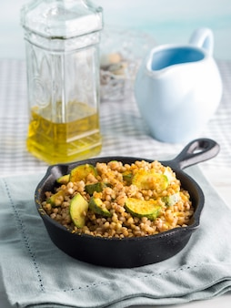 Buckwheat with zucchini and turmeric in skillet