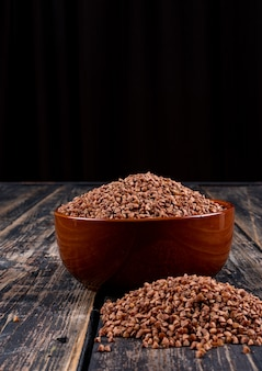 Buckwheats in a bowl and alongside, on a dark wooden . side view, vertical