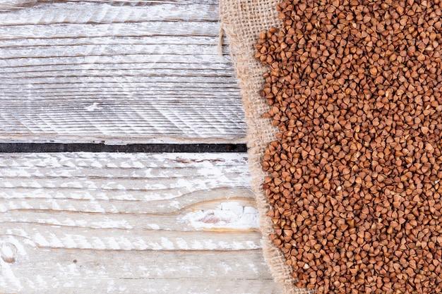 Grano saraceno su tela di sacco e legno bianco. vista dall'alto. spazio per il testo