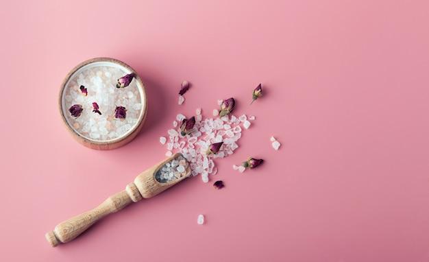 スパとバス用の塩の結晶は、コピースペースとピンクの背景に散在しています。バラの花びらとbudのエッセンシャルオイル。代替医療、リラクゼーション、体呼吸の概念
