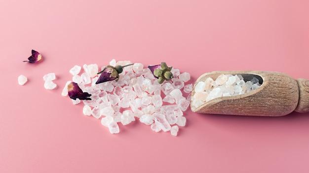 スパとバス用の塩の結晶は、コピースペースとピンクの背景に散在しています。バラの花びらとbudのエッセンシャルオイル。代替医療、リラクゼーション、体呼吸の概念。エコ。