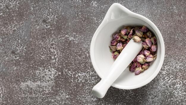 乳鉢と乳棒とバラのbudとコピースペースのフラットレイアウト