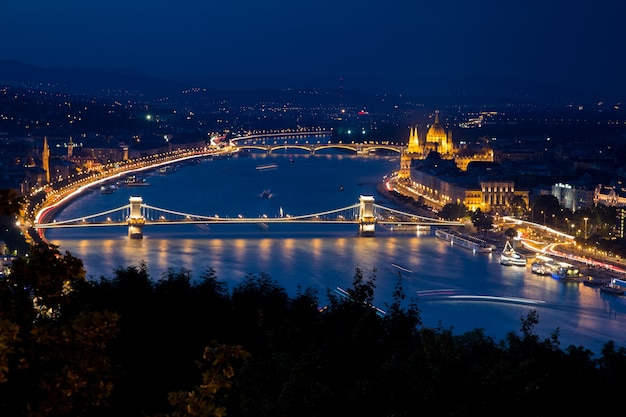 Buda castle surrounded by buildings and lights during the night in budapest