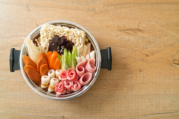 Budae jjigae или budaejjigae (армейское тушеное мясо или армейское базовое тушеное мясо). он полон кимчи, спама, сосисок, лапши рамэн и многого другого - популярного корейского стиля еды в горячем горшке.