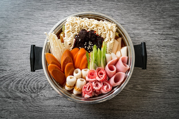 Budae jjigae или budaejjigae (армейское тушеное мясо или армейское базовое тушеное мясо). он полон кимчи, спама, сосисок, лапши рамен и многого другого - популярного корейского стиля еды в горячем горшке.