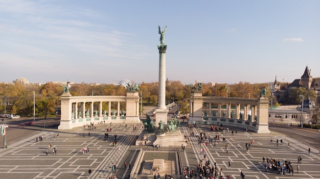 Budapest, hungary - aerial shot from drone on angel sculpture from on the top of heroes' square and the skyline of budapest