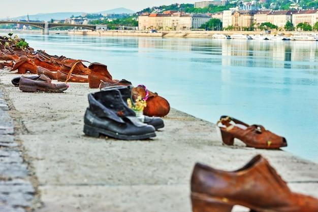 Будапешт, венгрия-4 мая 2016: историческая скульптура \ художественная установка «обувь на дунае» в память о евреях, убитых во время второй мировой войны. сосредоточьтесь на закулисье.