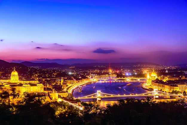 Budapest panorama with parliament and bridges during blue hour sunset.