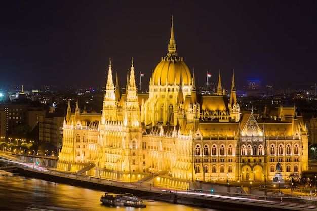 Budapest parliament building at night with dark sky and reflection in danube river