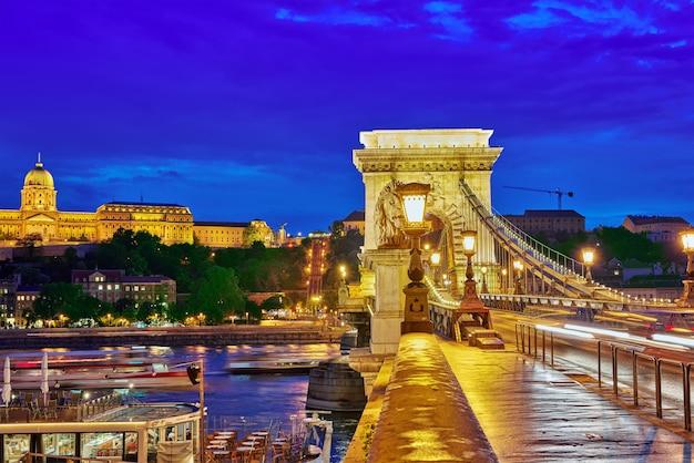 Будапештский королевский замок и цепной мост сечени в сумерках от реки дунай, венгрия