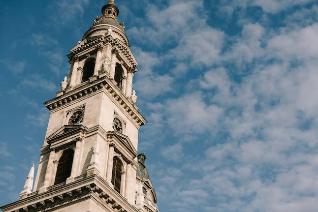 부분적으로 흐린 푸른 하늘 배경에 대해 부다페스트 성 스테판 성당