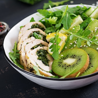 Buddha bowl dish with chicken fillet, avocado, cucumber, fresh arugula salad and sesame. detox and healthy keto diet bowl concept. overhead