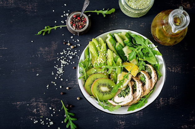 Buddha bowl dish with chicken fillet, avocado, cucumber, fresh arugula salad and sesame