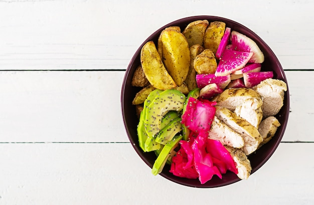 Buddha bowl dish with chicken fillet, beked potato, avocado, cabbage, watermelon radish and chia seeds. detox and healthy food bowl concept. top view