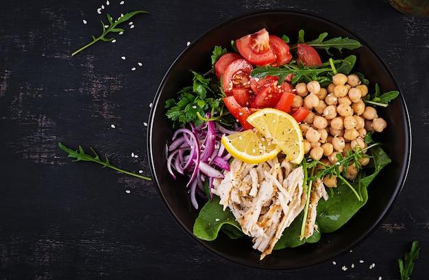 Чаша будды с куриным филе, нутом, помидорами, красным луком, свежим зеленым салатом и семенами кунжута. здоровое сбалансированное питание. вид сверху, сверху, копировать пространство
