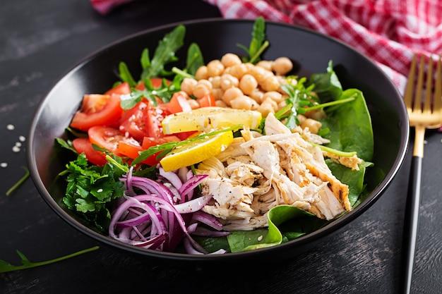 Чаша будды с куриным филе, нутом, помидорами, красным луком, свежим зеленым салатом и семенами кунжута. здоровое сбалансированное питание.