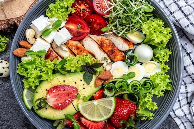 치킨 필레, 퀴노아, 아보카도, 아보카도, 페타 치즈, 메추라기 알, 딸기, 견과류, 양상추를 곁들인 부처 그릇 요리. 해독과 건강에 좋은 슈퍼푸드 그릇 개념. 음식 조리법 배경입니다.