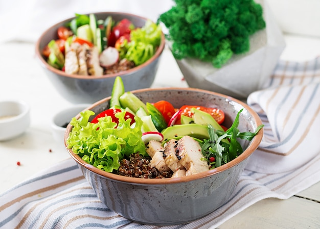 Buddha bowl dish with chicken fillet, quinoa, avocado, sweet pepper, tomato, cucumber, radish, fresh lettuce salad and sesame. detox and healthy superfoods breakfast bowl concept.