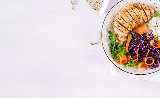 치킨 필렛, 쌀, 붉은 양배추, 당근, 신선한 양상추 샐러드와 참깨 부처 그릇 요리.