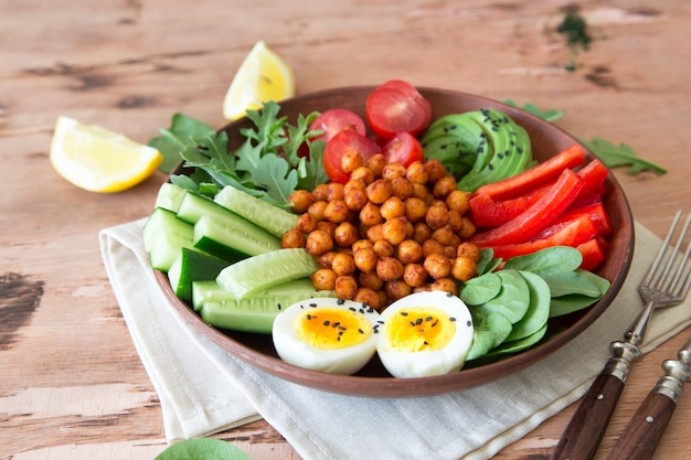 Buddha bowl, healthy and balanced food. fried chickpeas, cherry tomatoes, cucumbers, paprika, eggs, spinach, arugula