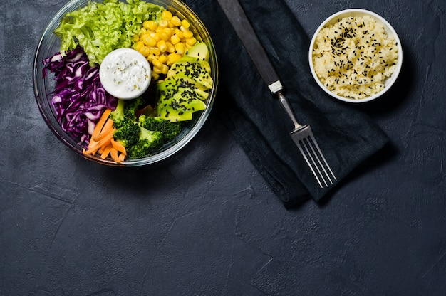 Buddha bowl, healthy and balanced food. ingredients broccoli, corn, carrots, couscous, lettuce, cabbage, sauce.