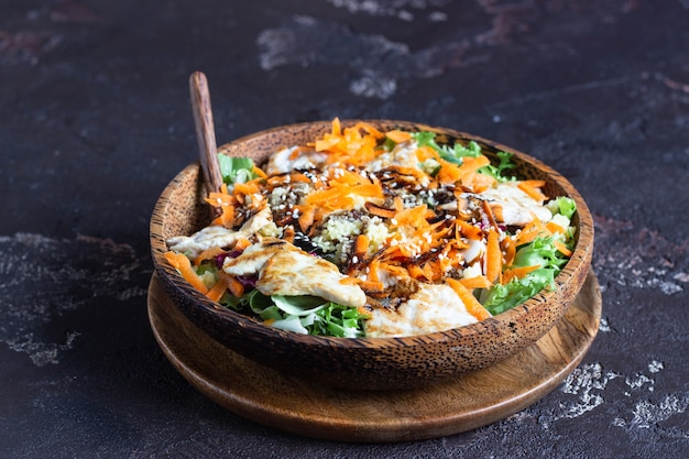 Buddha bowl lunch with couscous, turkey, carrot, salad mix and sesame.