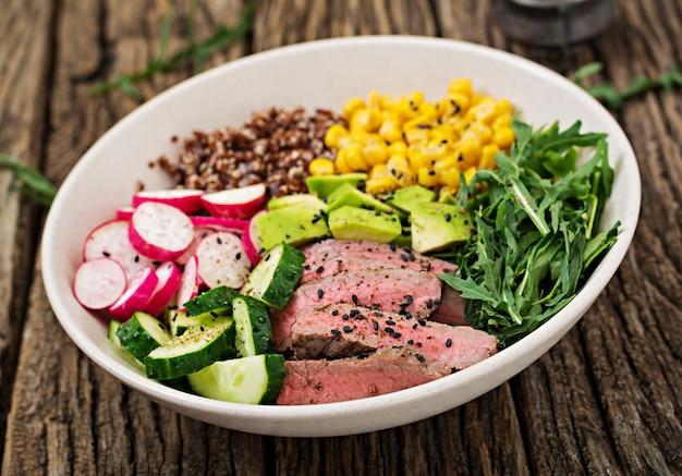 Обед будды с жареным бифштексом и квиноа, кукурузой, авокадо, огурцом и рукколой на деревянном столе
