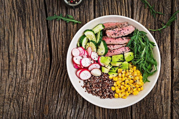 Buddha bowl lunch with grilled beef steak and quinoa, corn, avocado, cucumber and arugula