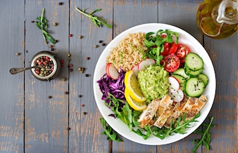 Buddha bowl lunch with grilled chicken and quinoa, tomato, guacamole and arugula.  Top vie