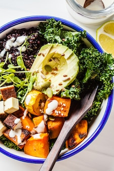 Buddha bowl salad with black rice, avocado, tofu, sweet potato, kale and tahini dressing