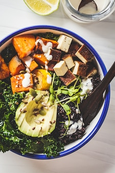 Buddha bowl salad with black rice, avocado, tofu, sweet potato, kale and tahini dressing
