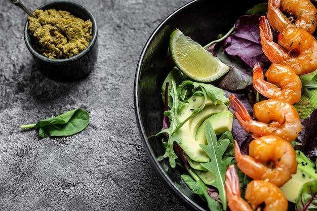 Чаша будды с авокадо, свежим салатом, креветками на гриле и соусом песто. кето-диета. меню рецепт место для текста, вид сверху.