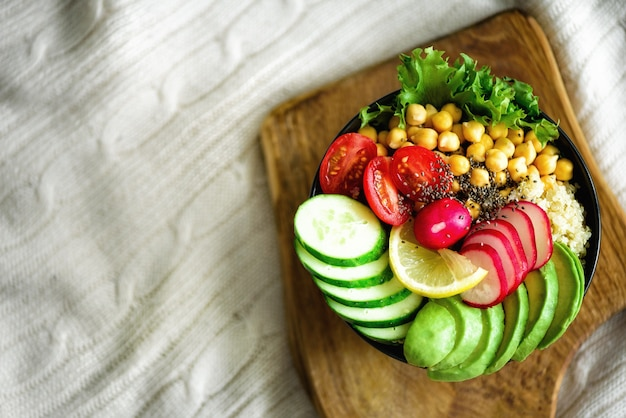 Buddha bowl with avocado, quinoa, cucumber, radish, salad, lemon, cherry tomatoes, chickpea, chia seeds on textile