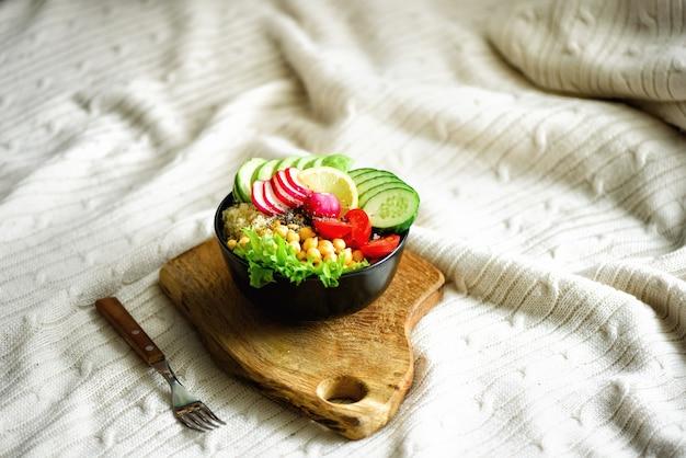 Buddha bowl with avocado, quinoa, cucumber, radish, salad, lemon, cherry tomatoes, chickpea, chia seeds on textile