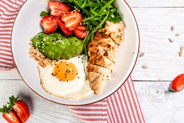 Buddha bowl with chicken, arugula and strawberries. keto diet food recipe background. close up
