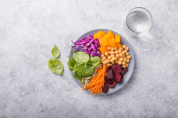 Buddha bowl with  chickpea, beetroot, fresh spinach, pumpkin and purple cabbage, glass of water. concept for  healthy vegetarian detox balanced  meal. top view. copy space.