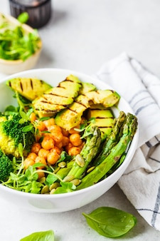 Buddha bowl with grilled avocado, asparagus, chickpeas, pea sprouts and broccoli