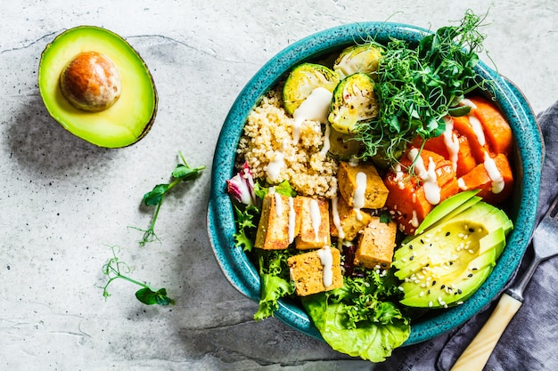 Buddha bowl with quinoa, tofu, avocado, sweet potato, brussels sprouts and tahini dressing