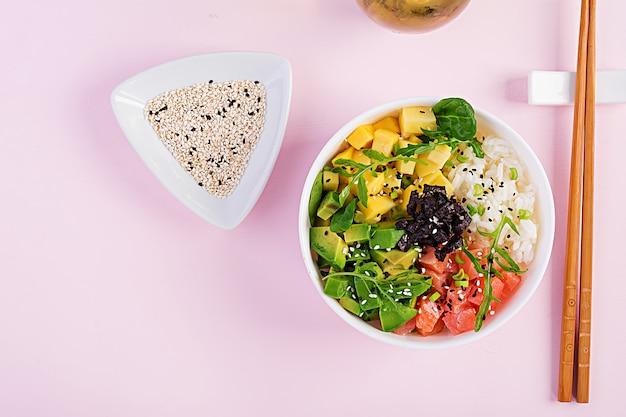 Buddha bowl with rice, mango, avocado and salmon