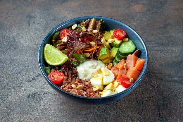 Чаша будды с лососем, помидорами, овощами и диким рисом, авокадо и огурцами в голубой тарелке.