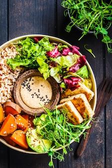 Buddha bowl with tofu, avocado, rice, seedlings, sweet potato and tahini dressing.